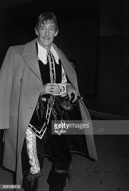 Peter O'Toole dressed as a musketeer carrying a coffee cup and a cigarette circa 1970 New York