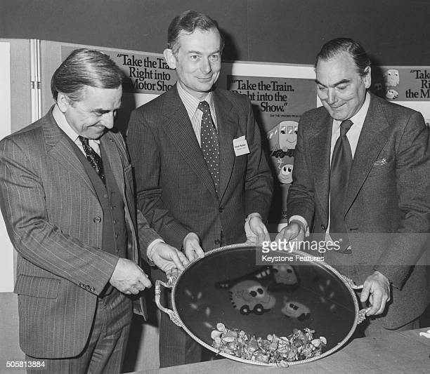 Peter Parker Chairman of British Rail with David Plastow President of the Society of Motor Manufacturers and Traders and Mr Weighall admiring a jelly...
