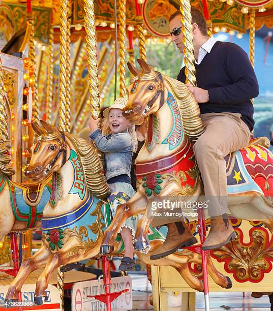 Peter Phillips and daughter Savannah Phillips ride on a merrygoround as they attend day 4 of the Royal Windsor Horse Show in Home Park on May 16 2015...