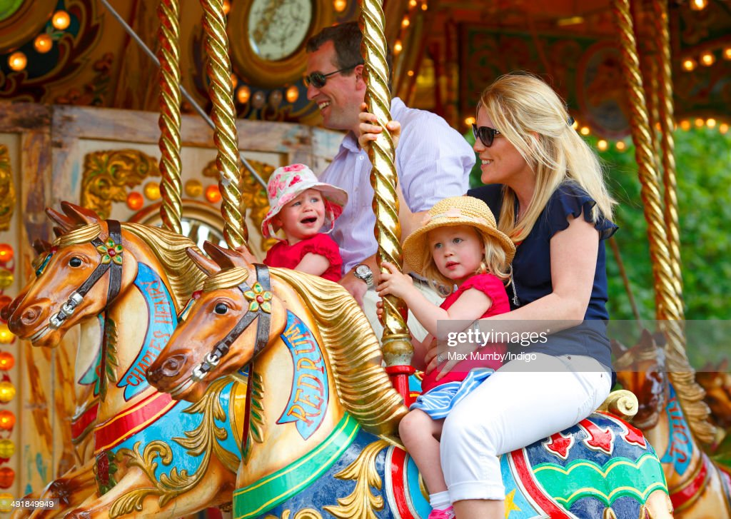 Peter Phillips with daughter Isla Phillips and Autumn Phillips with daughter Savannah Phillips ride a merry go round during day 4 of the Royal Windsor Horse Show at Home Park on May 17, 2014 in Windsor, England.
