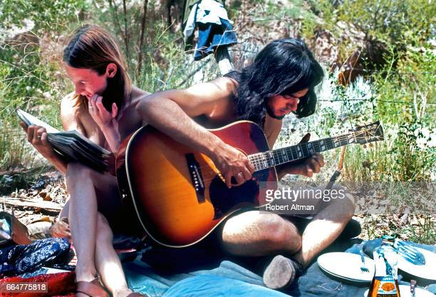 Peter Pizzitola plays a guitar as a lady reads a book as they are visiting from San Francisco and living in commune circa July 1969 in Tecate New...