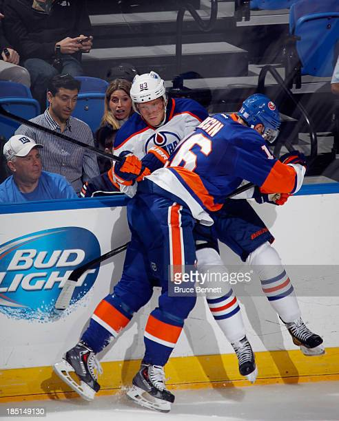 Peter Regin of the New York Islanders checks Ales Hemsky of the Edmonton Oilers into the boards at the Nassau Veterans Memorial Coliseum on October...