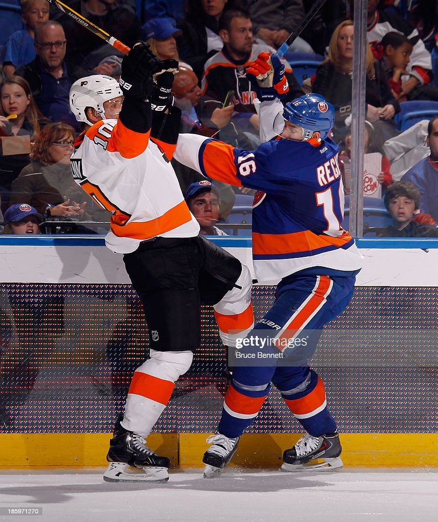 Peter Regin #16 of the New York Islanders checks Brayden Schenn #10 of the Philadelphia Flyers during the second period at the Nassau Veterans Memorial Coliseum on October 26, 2013 in Uniondale, New York.