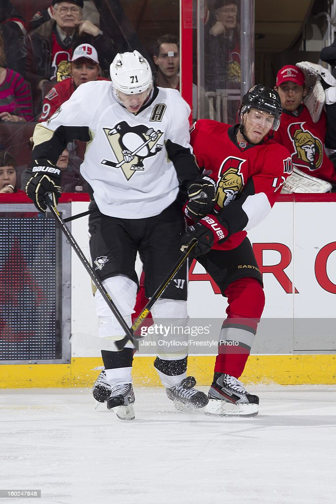 Peter Regin #13 of the Ottawa Senators battles for the loose puck against Evgeni Malkin #71 of the Pittsburgh Penguins during an NHL game at Scotiabank Place on January 27, 2013 in Ottawa, Ontario, Canada.