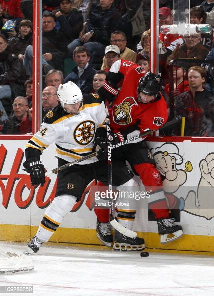 Peter Regin of the Ottawa Senators battles for the loose puck with Dennis Seidenberg of the Boston Bruins at Scotiabank Place on February 18 2011 in...