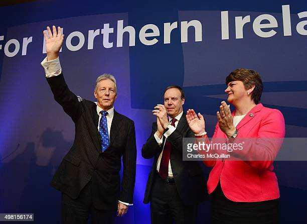 Peter Robinson waves goodbye to the party faithful watched by Nigel Dodds and Arlene Foster after his final leaders speech during the Democratic...