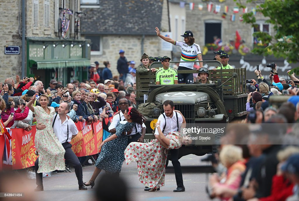 Peter Sagan of Slovakia waves to the crowd as team leader Alberto Contador of Spain sits atop a first world war military vehicle as the Tinkoff team arrive during the team presentations on June 30, 2016 in Sainte-Mere-Eglise, France.