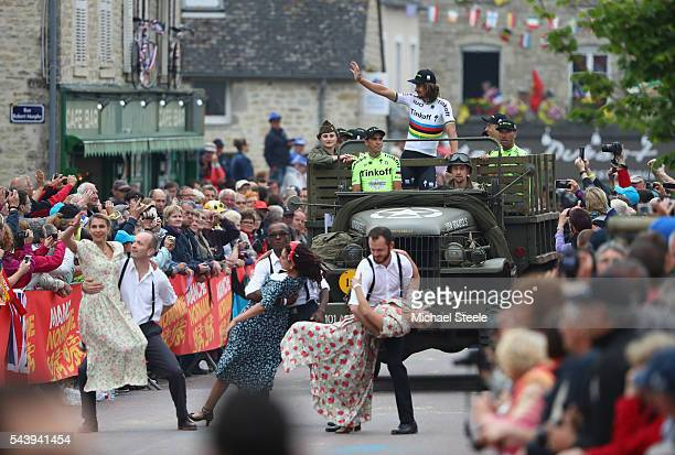Peter Sagan of Slovakia waves to the crowd as team leader Alberto Contador of Spain sits atop a first world war military vehicle as the Tinkoff team...