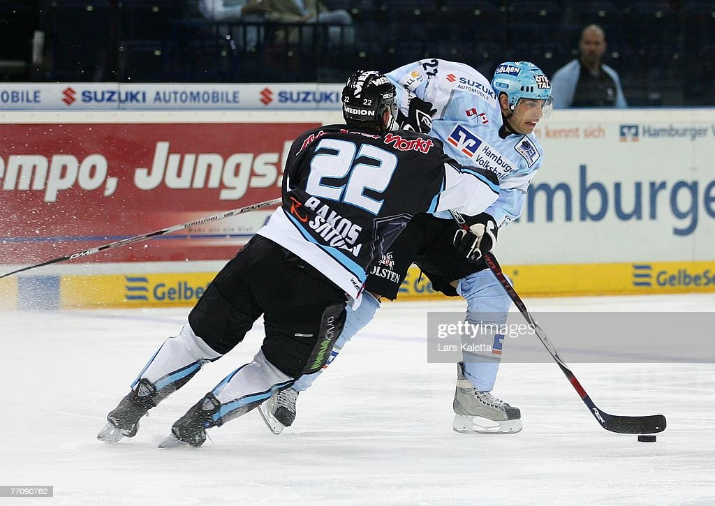 Peter Sarno of Hamburg fights for the puck with Michael Bakos of Ingolstadt during the DEL match between Hamburg Freezers and ERC Ingolstadt at the...