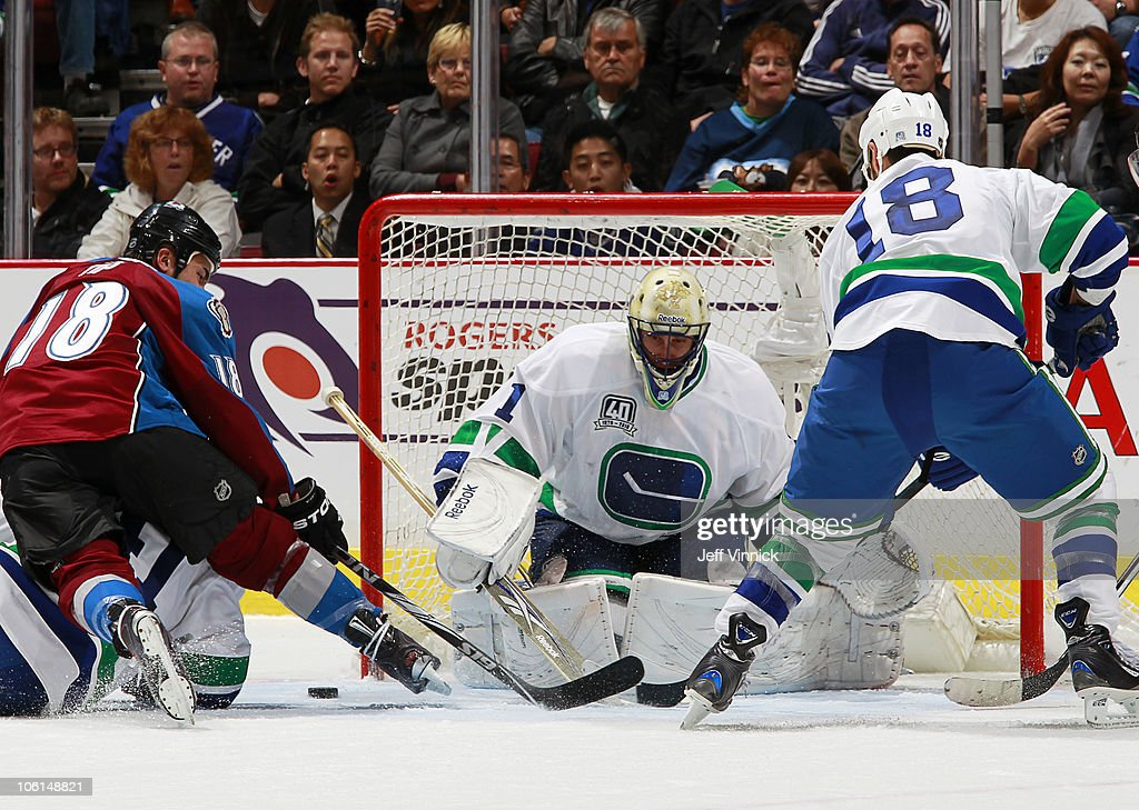 Peter Schaefer #18 of the Vancouver Canucks looks on as teammate Roberto Luongo #1 makes a save off the shot of Brandon Yip #18 of the Colorado Avalanche at Rogers Arena on October 26, 2010 in Vancouver, British Columbia, Canada. Vancouver won 4-3 in overtime.