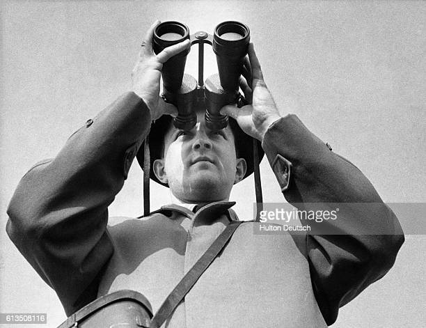 Peter Scott the naturalist and Chairman of the World Wildlife Fund for Nature looks through a pair of binoculars ca 1940