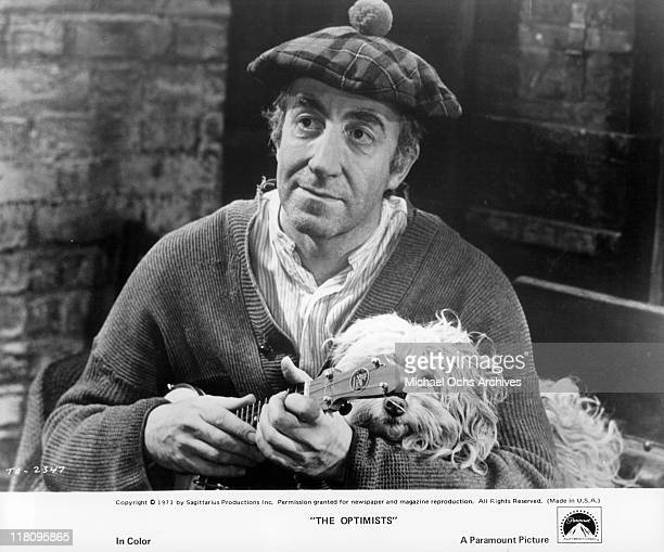 Peter Sellers plays ukulele with dog in a scene from the film 'The Optimists' 1973