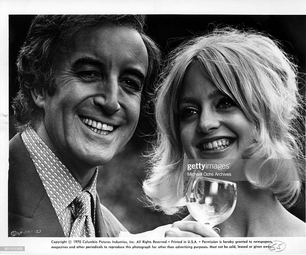 Peter Sellers smiles with Goldie Hawn in a scene from the movie 'There's a Girl in My Soup', circa 1970.