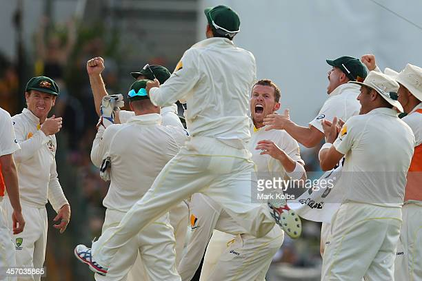 Peter Siddle of Australia and the Australian team celebrate the wicket of Ian Bell of England after he was given out by the DRS during day four of...