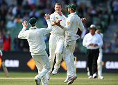 Peter Siddle of Australia is congratulated by Steven Smith and Nathan Lyon after dismissing Jason Holder of the West Indies during day two of the...