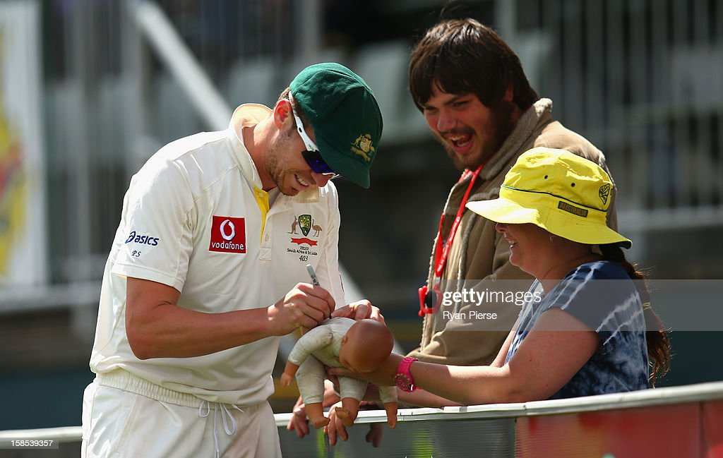 Peter Siddle of Australia signs a doll for a fan during day five of the First Test match between Australia and Sri Lanka at Blundstone Arena on December 18, 2012 in Hobart, Australia.