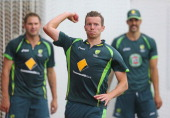 Peter Siddle of Australia throws the ball as Ryan Harris and Mitchell Johnson look on during an Australian Ashes training session the at Melbourne...