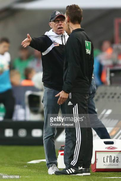 Peter Stoeger coach of Koeln argues with the fourth official Christian Bandurski during the Bundesliga match between 1 FC Koeln and Eintracht...