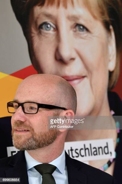 Peter Tauber secretary general of Germany's conservative Christian Democratic Union stands in front of a portrait of German Chancellor Angela Merkel...