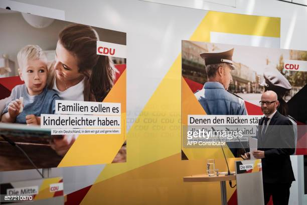 Peter Tauber secretary general of Germany's conservative Christian Democratic Union party presents campaign posters for the upcoming general...