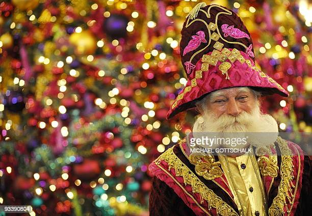 Peter the Santa Claus of Berlin's most famous department store KaDeWe poses on front of a colourful Christmas tree during the presentation of the...