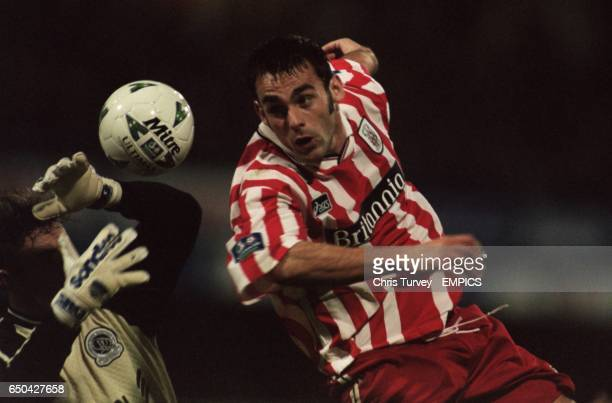 Peter Thorne of Stoke City gets in a header despite the attentions of Queens Park Rangers' goalkeeper Tony Roberts