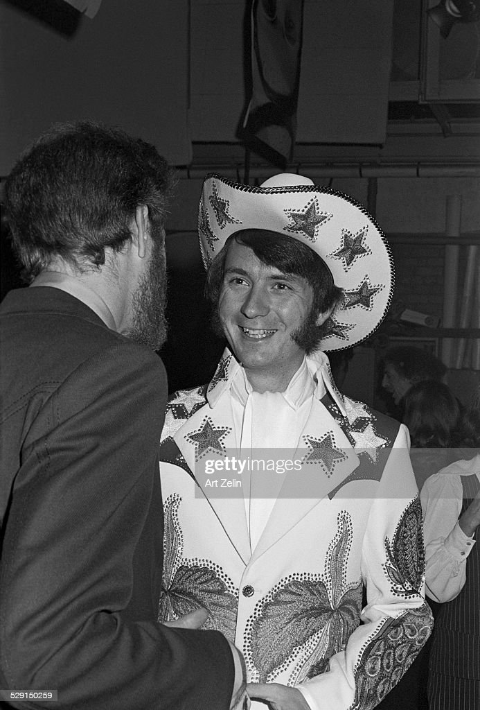 Peter Tork of the Monkees wearing decorated Western wear with stars in conversation circa 1970 New York