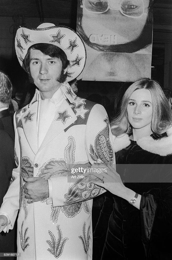 Peter Tork of the Monkees with a young lady He is wearing a dress Western outfit decorated with stars and peacocks she is wearing a velvet fur...