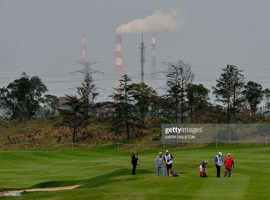Peter Uihlein (2nd L) and John Daly both of the US (R) prepares to tee off in front of smokestacks at the 7th hole during day two of the BMW Shanghai Masters golf tournament at the Lake Malaren Golf Club in Shanghai on October 25, 2013. The 7 million USD event is being held for the second time at the Lake Malaren Golf Club. AFP PHOTO/Mark RALSTON