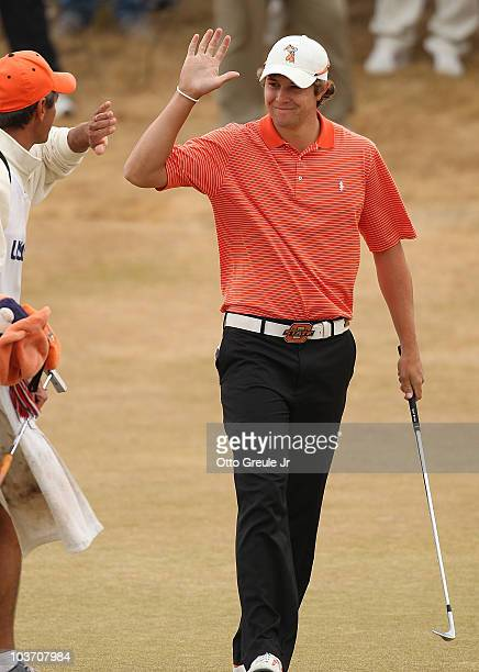 Peter Uihlein is congratulated by caddie Alan Bratton after chipping in on the 18th hole on the final day of the US Amateur Golf Championship on...