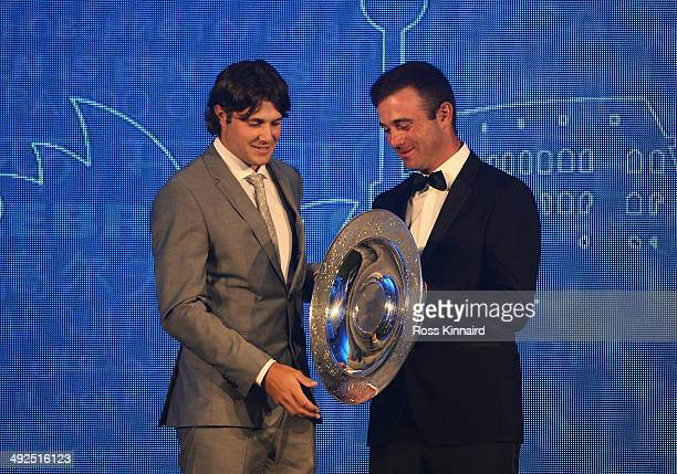 Peter Uihlein of the United States receives the 2013 Sir Henry Cotton Rookie of the Year award from Ricardo Santos of Portugal during the European...