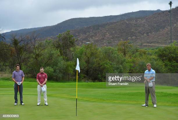 Peter Uihlein of USA Branden Grace of South Africa and Ernie Els of South Africa observes a minutes silence after the death of South African...