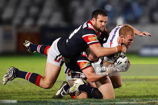 Peter Wallace of the Broncos is tackled over the top by Nate Myles of the Roosters during the round six NRL match between the Sydney Roosters and the...