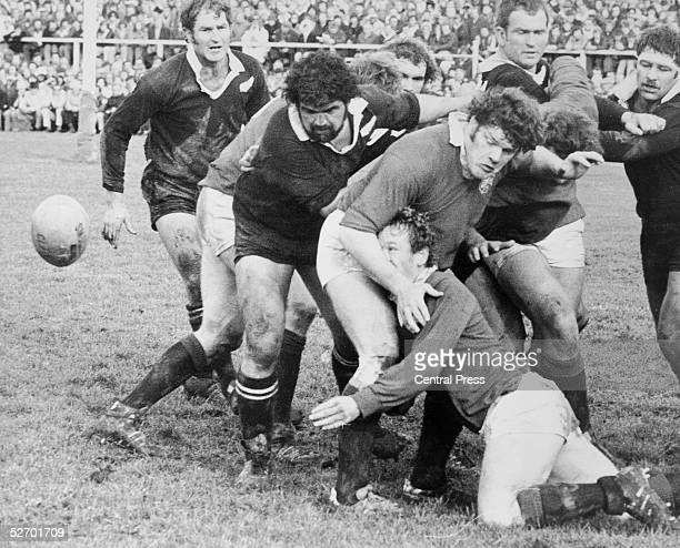 Peter Wheeler of the British Lions goes down as he passes the ball supported by Fran Cotton during the second rugby test match against the New...