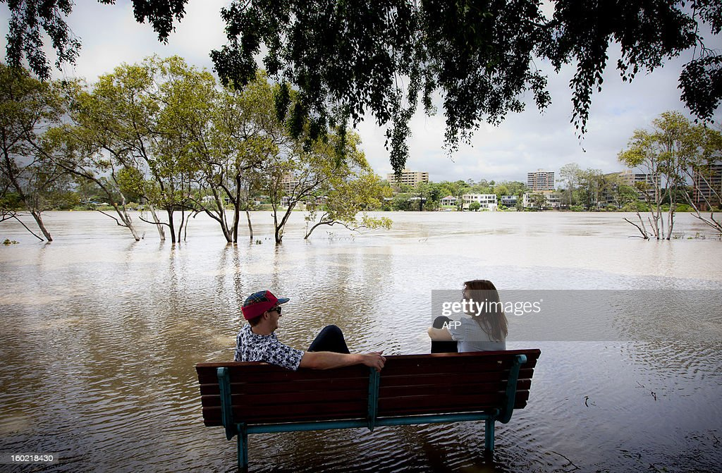 Peter Wison (L) and Beata Jaremko sit on a bench surrounded by floodwaters as the Brisbane River brakes its banks at West End in Brisbane on January 28, 2013. Helicopters plucked dozens of stranded Australians to safety in dramatic rooftop rescues on January 28 as severe floods swept the northeast, killing three people and inundating thousands of homes.AFP PHOTO / Patrick HAMILTON