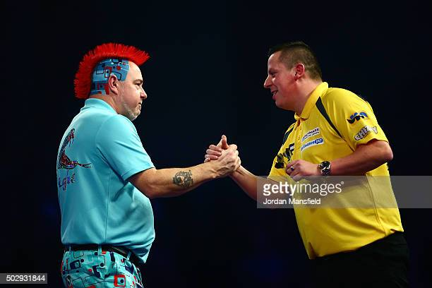 Peter Wright of Scotland shakes hands with Dave Chisnall of England after victory in their third round match on Day Twelve of the 2016 William Hill...