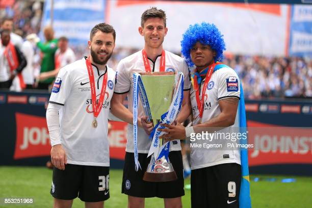 Peterborough United goalscorers Josh McQuoid Shaun Brisley and Britt Assombalonga celebrate with the trophy