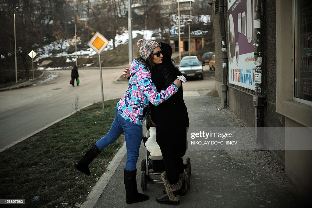 Petia Kotcheva, 24, hugs a friend from the neighborhood, a few days before her departure from Bulgaria on December 20, 2013 in Gabrovo, about 200km east of capital Sofia. Petia decided to quit university to settle in Amsterdam and work as a waitress in a club. 'It's worthless to get a diploma that leads only to unemployment or a salary of 450 leva a month (US $315)''. On January 1, nine countries including Britain, France and Germany still imposing restrictions on Bulgarian and Romanian workers will lift them. AFP PHOTO / NIKOLAY DOYCHINOV