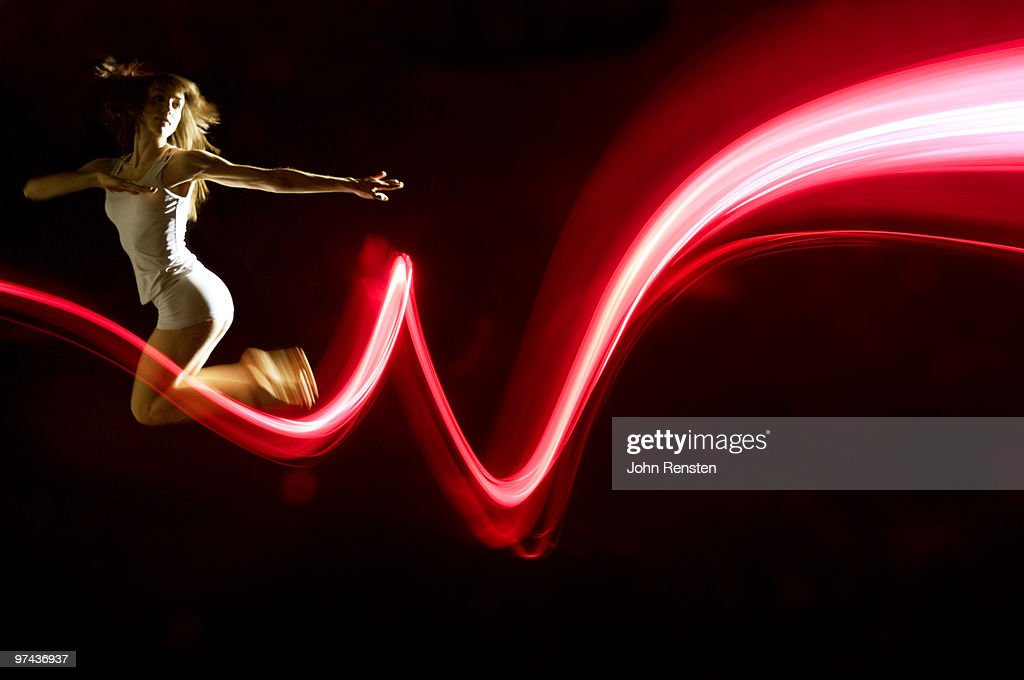 petit dancer jumps  with red abstract light trail : Stock Photo