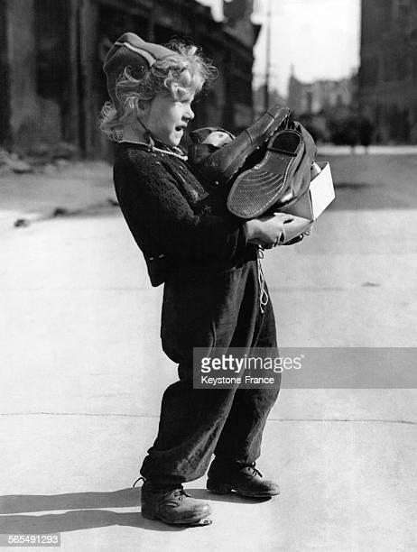 Petit garçon blond pliant sous le poids du carton de chaussures d'adultes qu'il tient dans ses bras à Hanovre en Allemagne le 19 avril 1945
