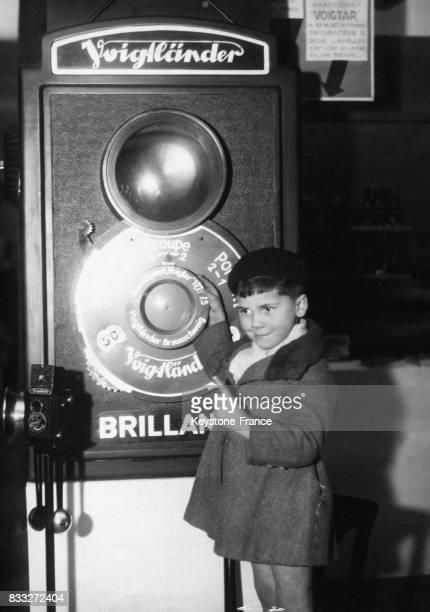 Petit garçon posant à côté d'un appareil photo géant sur le stand de la marque allemande Voiglander à l'occasion de l'ouverture du Salon de la photo...