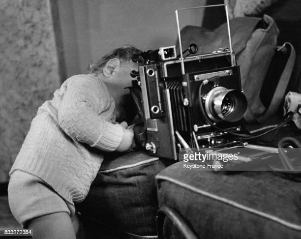 Petit garçon regardant dans un vieux modèle d'appareil photo