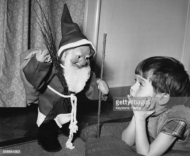 Petit garçon regardant un Père Noël miniature en novembre 1960