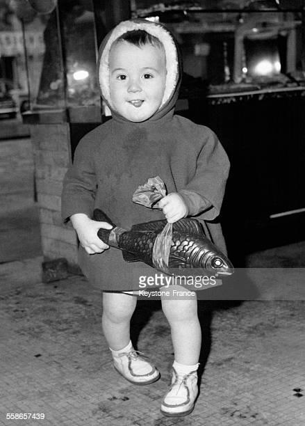 Petit garçon tenant son poisson au chocolat tire la langue à l'idée de le croquer à Paris France le 1 avril 1962