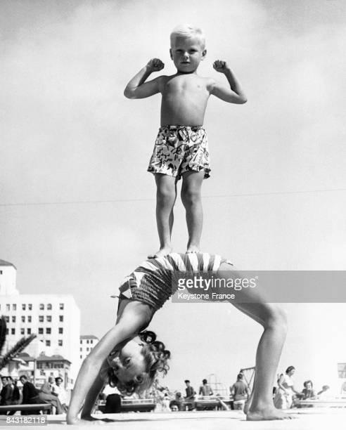 Petit Tarzan debout sur le ventre de sa soeur qui fait le pont sur la plage de Santa Monica Californie EtatsUnis