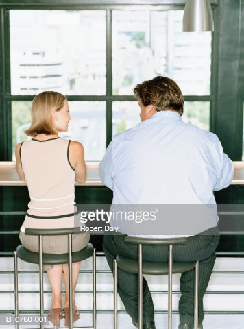 Petit woman and overweight businessman at table, rear view