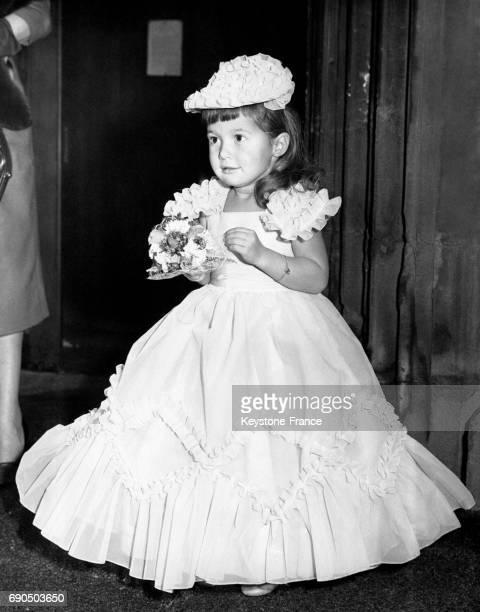 Petite demoiselle d'honneur portant un bouquet de fleurs