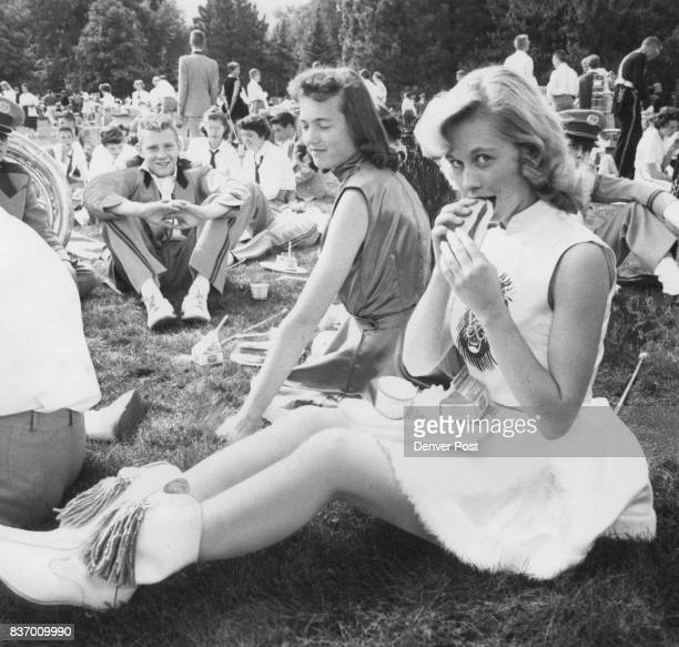 Petite Mavis Doetz Littleton High School majorette gives the photographer a sidelong glance as she munches a hotdog on the CU campus before the game...