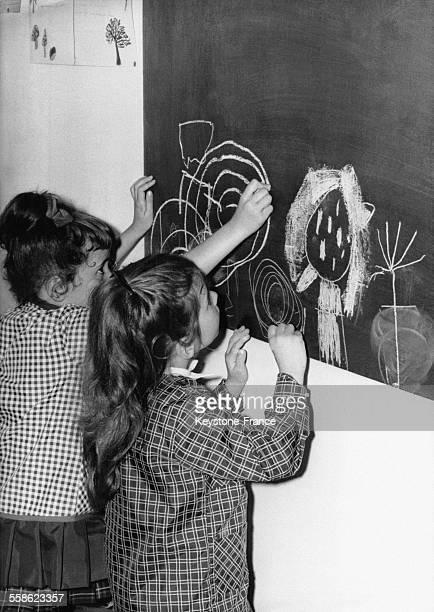Petites filles dessinant à la craie au tableau lors de la rentrée scolaire en France le 15 septembre 1967