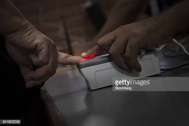 A petition signee uses a fingerprint scanner to validate a signature at a National Electoral Council center in Caracas Venezuela on Monday June 20...